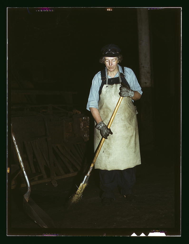 A woman in an apron sweeps in front of a dark background.