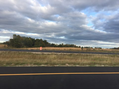 An image of the landscape from the window of a car going down the interstate. There are clouds, distant trees, and a small orange traffic construction cone in the background.