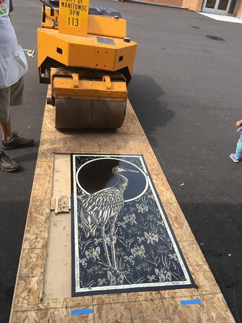 A carved and inked wood block with an image of a heron on it sits on the ground waiting for paper. Behind it a streetroller waits to press it.