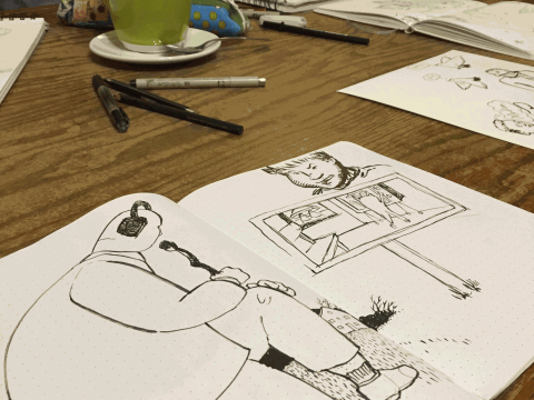 An image of sketchbooks with drawings in them open on a table.