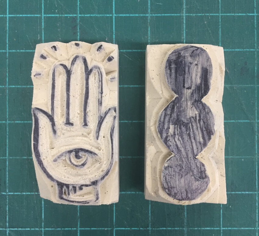 An image of two small erasers carved for relief printing. One eraser shows the hamsa, a symbol with an eye in a hand. The other eraser shows three circles touching.