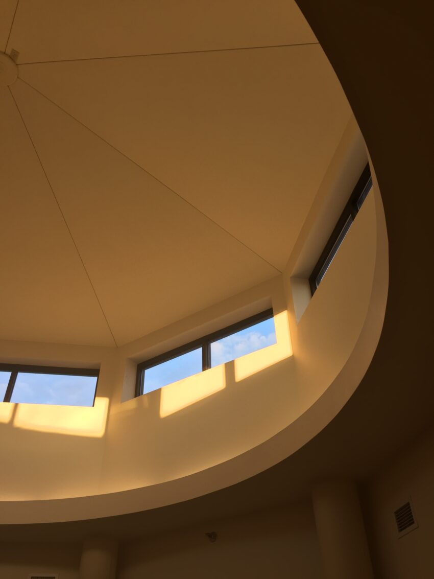 An image of the ceiling of the second floor of the Bush Art Center. There are rectangular windows set into a circular large cupola-type space. It is late in the day and the yellow light comes through at a slant.