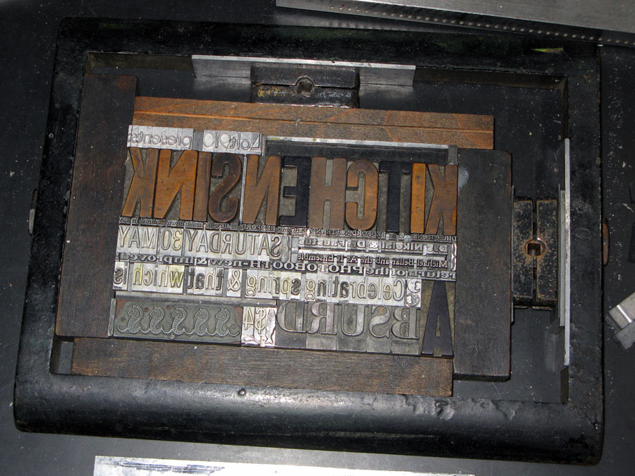 An image of letterpress type locked up and waiting for printing. Large wood letters read (backwards) KITCHENSINK.