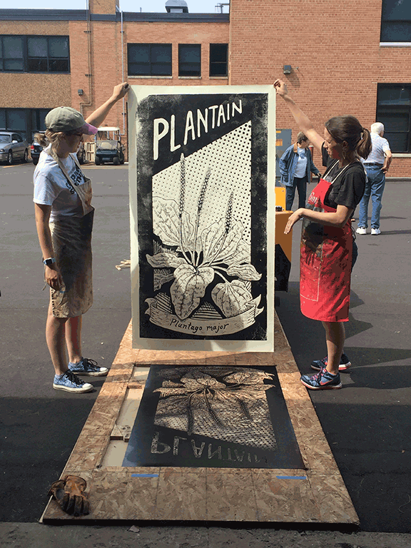 Two white women stand on a large relief print block and hold overhead the print they've just pulled.