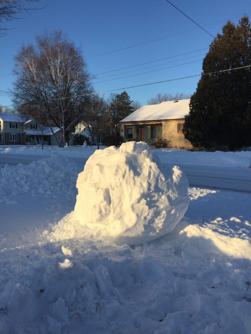 A large lumpy ball of snow catches low golden sunlight. A house is visible in the background.
